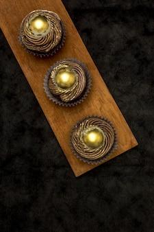 Bovenaanzicht van gouden cupcakes op houten bord