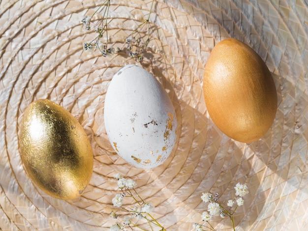 Bovenaanzicht van gouden gekleurde paaseieren op placemat