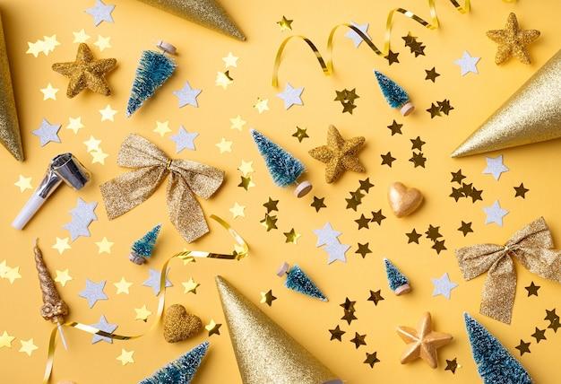 Bovenaanzicht van gouden kerst- en nieuwjaarsversieringen met confetti en geschenkdozen plat leggen