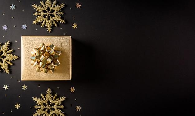 Bovenaanzicht van gouden kerstdozen en sneeuwvlok op zwarte muur met kopie ruimte voor tekst