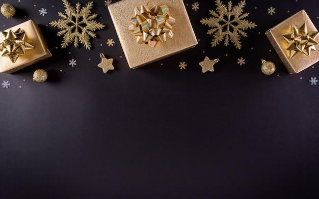 Bovenaanzicht van gouden kerstdozen en sneeuwvlok op zwarte muur,