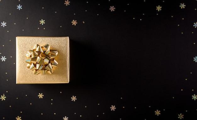 Bovenaanzicht van gouden kerstdozen op zwarte achtergrond met kopie ruimte voor tekst