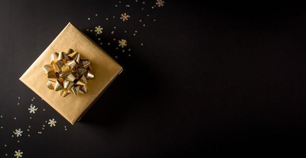 Bovenaanzicht van gouden kerstdozen op zwarte achtergrond