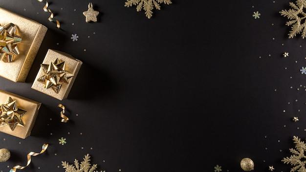 Bovenaanzicht van gouden kerstdozen op zwarte muur met kopie ruimte voor tekst.