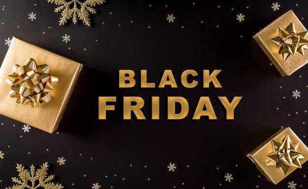 Bovenaanzicht van gouden kerstdozen op zwarte ondergrond met zwarte vrijdag-tekst