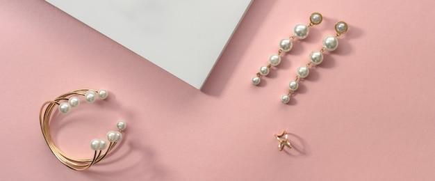 Bovenaanzicht van gouden parel armband en oorbellen op roze en witte ondergrond