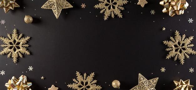 Bovenaanzicht van gouden sneeuwvlok, sterren en kerstbal op zwarte muur met kopie ruimte
