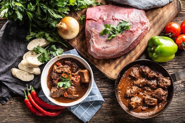 Bovenaanzicht van goulash-feest met maaltijd geserveerd op borden in de kom, ingrediënten en zijkanten.