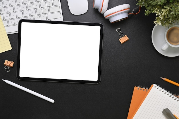 Bovenaanzicht van grafisch ontwerper werkplek met tablet, koffiekopje, notebook, hoofdtelefoon en toetsenbord op zwart leer.