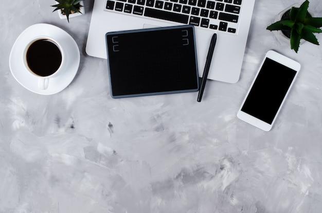 Bovenaanzicht van grafisch tablet, grafische pen, smartphone, laptop en een kopje zwarte koffie.