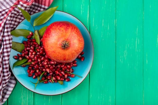 Bovenaanzicht van granaatappel en granaatappel bessen in plaat op geruite doek en groen oppervlak