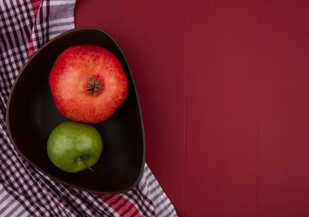 Bovenaanzicht van granaatappel met een groene appel in een kom met een rood geruite handdoek op een rood oppervlak