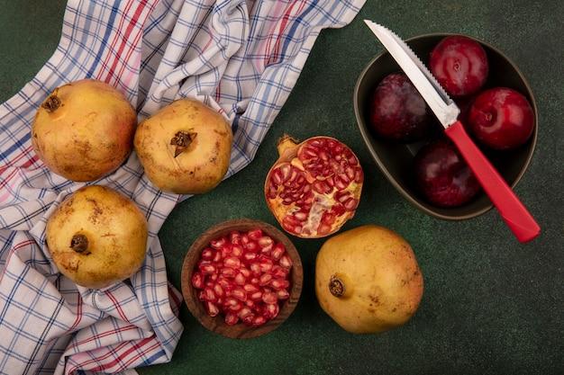 Bovenaanzicht van granaatappel zaden op een houten kom met plukken op een kom met mes met granaatappels geïsoleerd op een gecontroleerde doek op een groene achtergrond