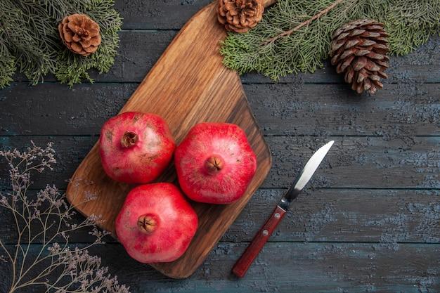 Bovenaanzicht van granaatappels aan boord van granaatappels op snijplank naast mes en spuce-takken met kegels