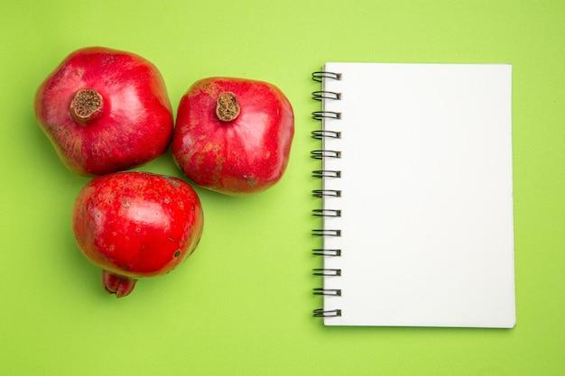 Bovenaanzicht van granaatappels rode rijpe granaatappels naast het witte notitieboekje