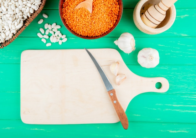 Bovenaanzicht van granen en peulvruchten in kommen en een houten snijplank met een mes op groene achtergrond