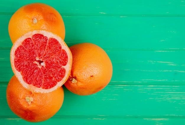 Bovenaanzicht van grapefruits aan de linkerkant en groene achtergrond met kopie ruimte