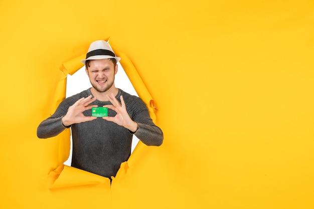 Bovenaanzicht van grappige jonge kerel met bankkaart in een gescheurde gele muur