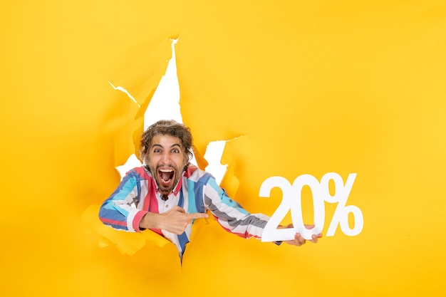 Bovenaanzicht van grappige jongeman met twintig procent in een gescheurd gat in geel papier in