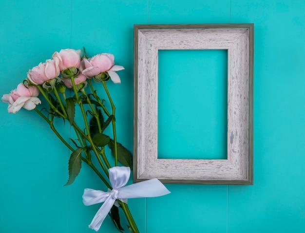 Bovenaanzicht van grijs frame met lichtroze rozen op een lichtblauw oppervlak