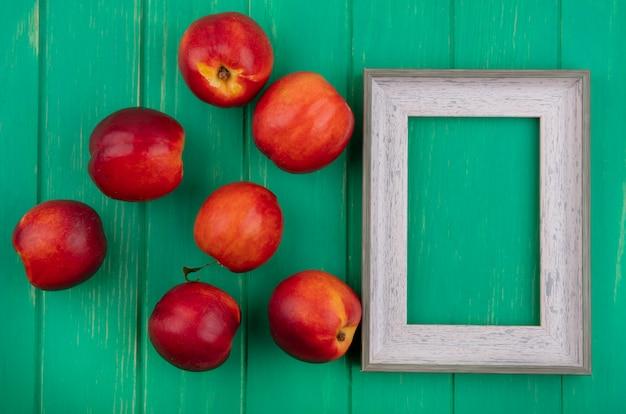 Bovenaanzicht van grijs frame met perziken op een groen oppervlak