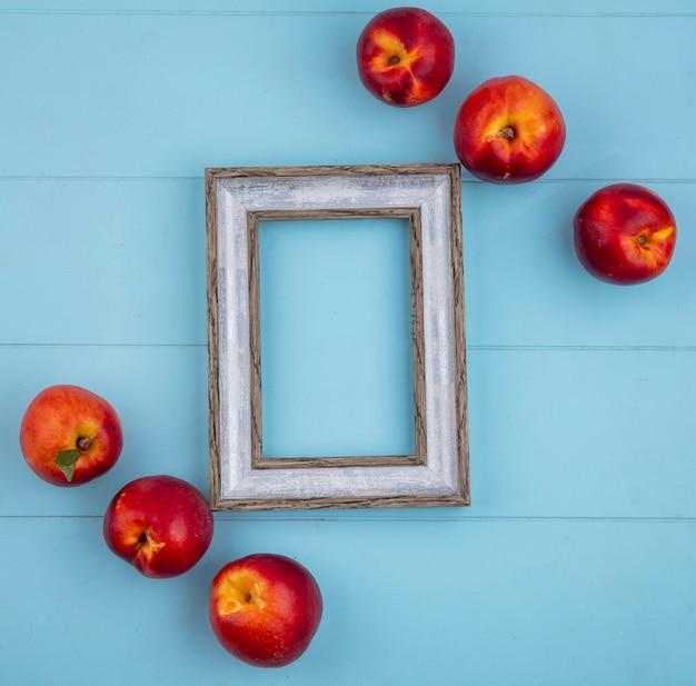 Bovenaanzicht van grijs frame met perziken op een lichtblauw oppervlak