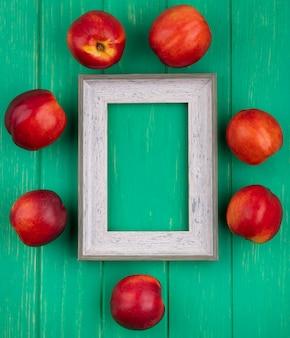 Bovenaanzicht van grijs frame met perziken rond op een groen oppervlak