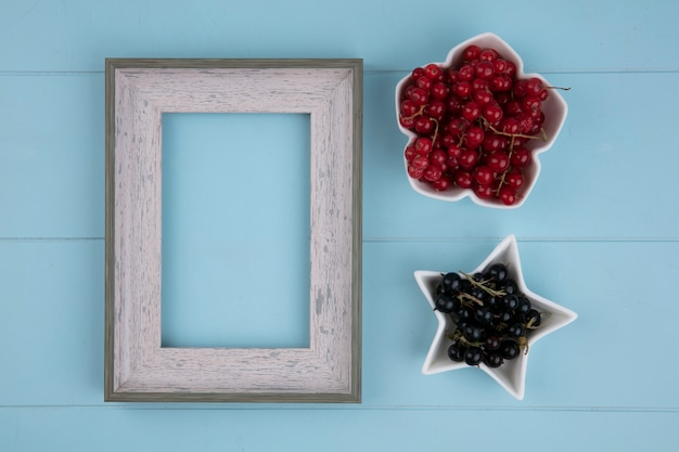 Bovenaanzicht van grijs frame met rode en zwarte bessen op een blauw oppervlak