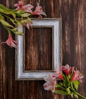 Bovenaanzicht van grijs frame met roze lelies op een houten oppervlak