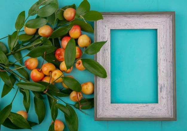 Bovenaanzicht van grijs frame met witte zoete kersen met bladtakken op een turkoois oppervlak