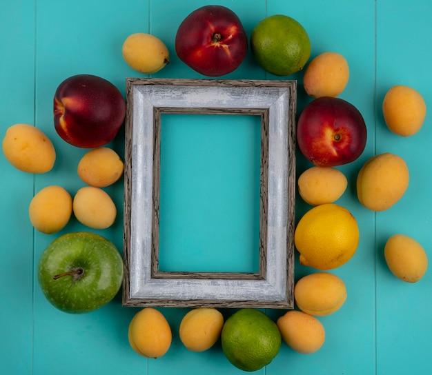 Bovenaanzicht van grijs frame perziken appels abrikozen citroen en limoen op een blauw oppervlak