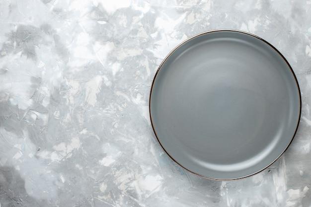 Bovenaanzicht van grijze plaat leeg op grijs bureau, keukenbord eten