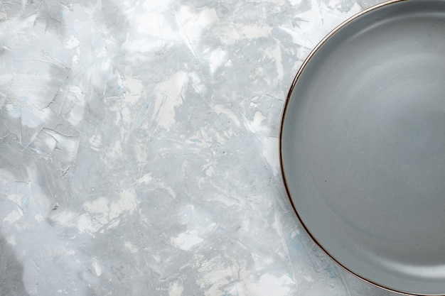 Bovenaanzicht van grijze plaat leeg op grijs-licht bureau, plaat voedsel keuken