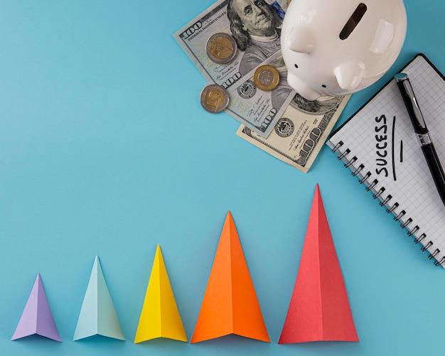Bovenaanzicht van groeikegels met bankbiljetten en spaarvarken