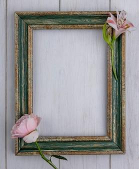 Bovenaanzicht van groenachtig gouden frame met licht roze roos en lelie op een grijze ondergrond