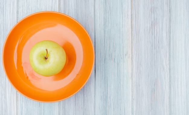 Bovenaanzicht van groene appel in plaat op houten achtergrond met kopie ruimte
