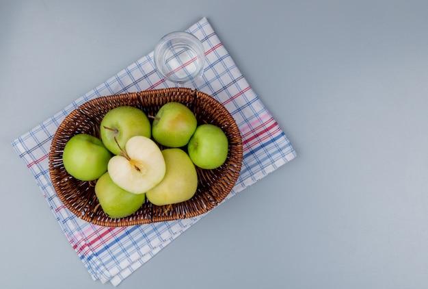 Bovenaanzicht van groene appels in mand en glas water op plaid doek en grijze achtergrond met kopie ruimte