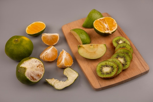 Bovenaanzicht van groene appels met plakjes kiwi op een houten keukenbord met mandarijnen geïsoleerd