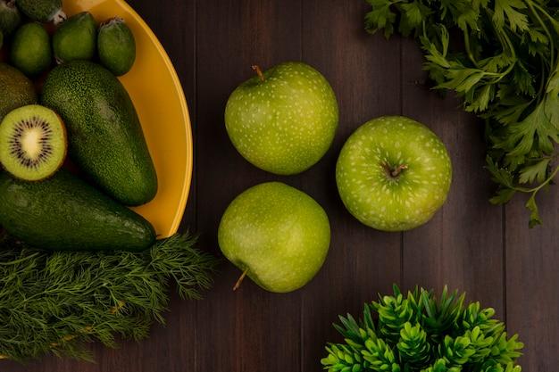 Bovenaanzicht van groene appels met vers fruit zoals avocado's feijoas en kiwi's op een gele plaat op een houten muur