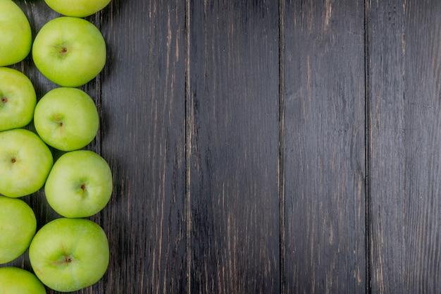 Bovenaanzicht van groene appels op houten achtergrond met kopie ruimte