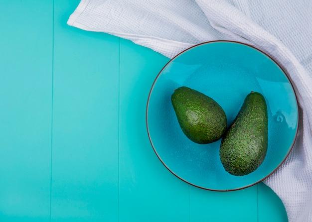 Bovenaanzicht van groene avocado's op een plaat op blauwe ondergrond