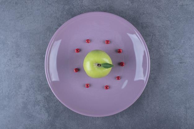 Bovenaanzicht van groene biologische verse appel op paarse plaat.