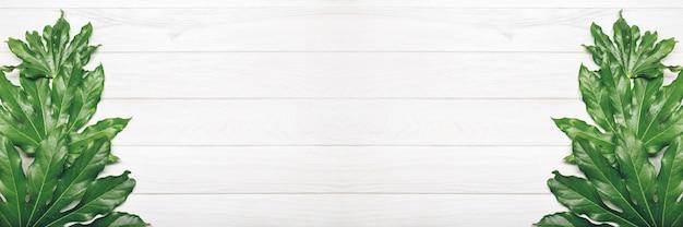 Bovenaanzicht van groene bladeren op witte houten achtergrond