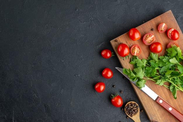 Bovenaanzicht van groene bundel verse, hele gesneden tomaten op een houten snijplankmes aan de linkerkant op een zwart verontrust oppervlak