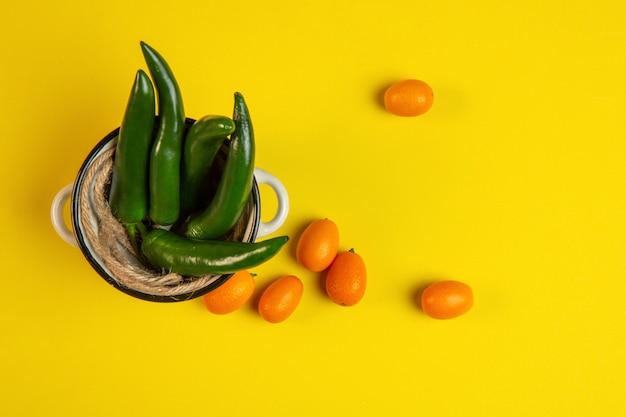 Bovenaanzicht van groene chili peper in een metalen pot en kumquat op geel