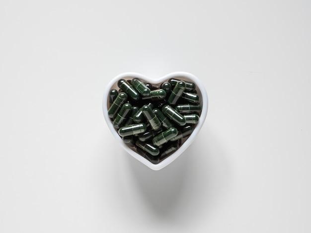 Bovenaanzicht van groene chlorella-pillen in witte hartvormige kom op witte achtergrond met kopieerruimte