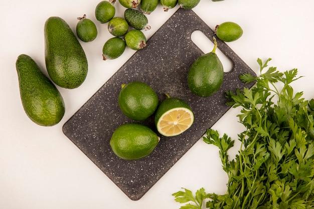Bovenaanzicht van groene citrusvruchten limoenen op een keukenbord met feijoas avocado's en peterselie geïsoleerd op een witte muur