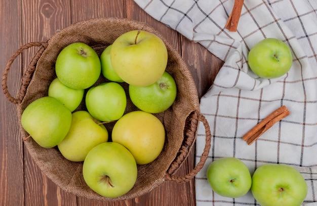 Bovenaanzicht van groene en gele appels in mand met kaneel op geruite doek en houten achtergrond