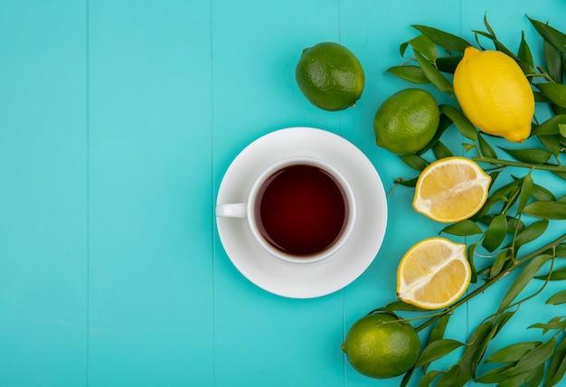 Bovenaanzicht van groene en gele citroenen met bladeren met een kopje thee op blauwe ondergrond