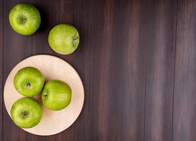Bovenaanzicht van groene en heerlijke appels op een houten keuken bord op een houten oppervlak